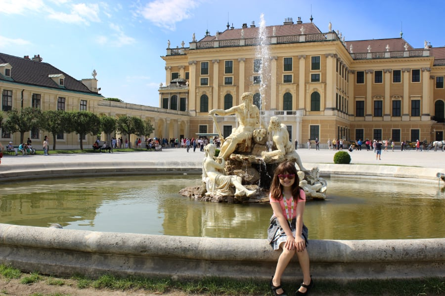 Little girl sitting on the edge of a fountain in front of an imposing orange and beige palace