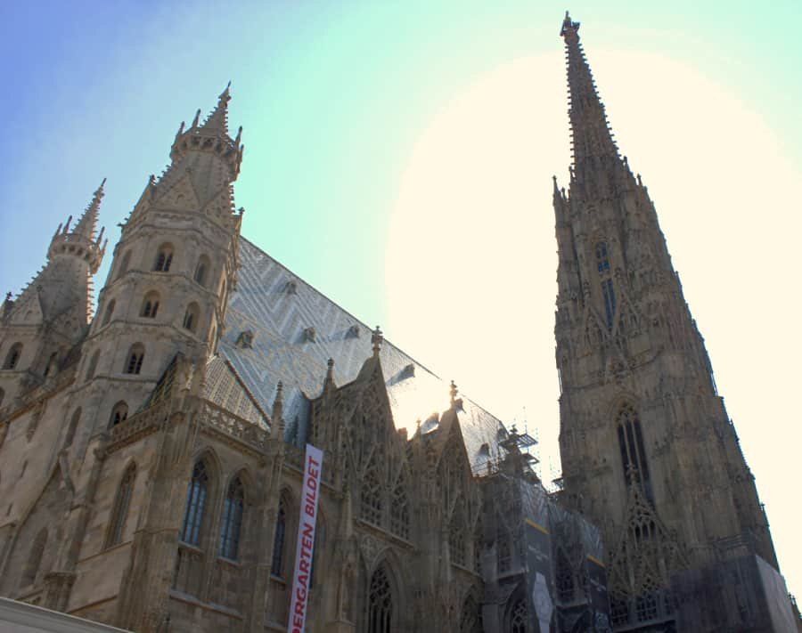 Looking up at a gothic orange and beige cathedral with the rightmost tower soaring toward the sky in Vienna