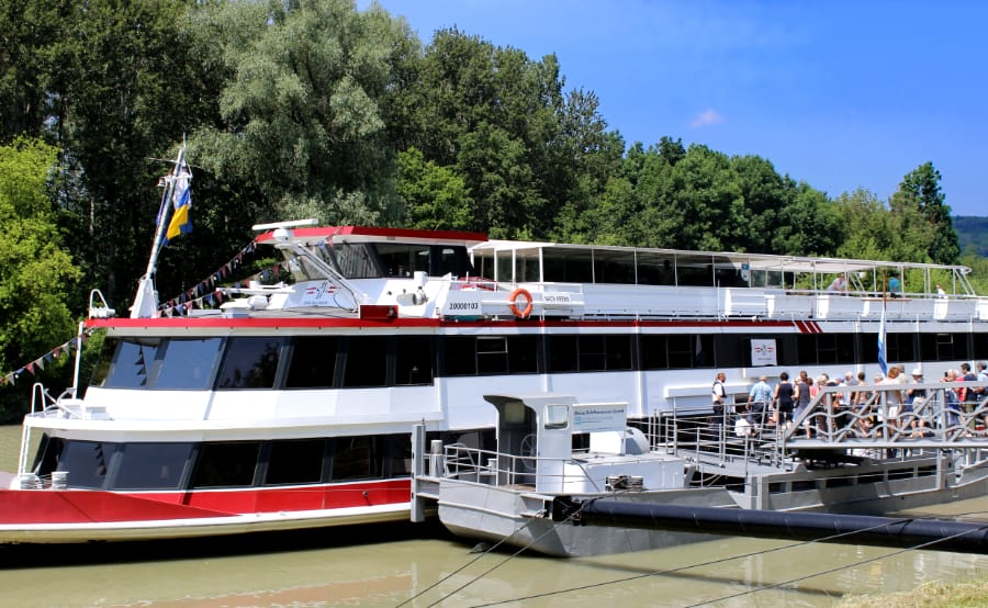 White yacht with red trim and dark windows docked on a river as people are getting on the boat to cruise on the Danube River toward Vienna