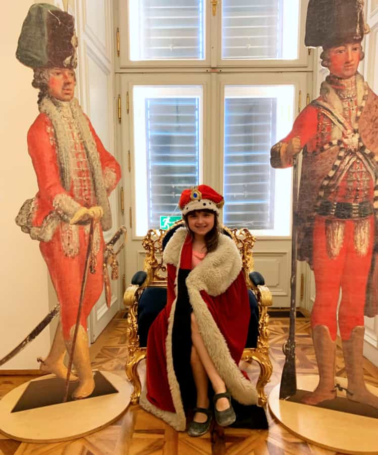 Little girl wearing a red regal robe and crown sitting on a chair with two large cutouts of royal men on each side at Schonbrunn's childrens museum