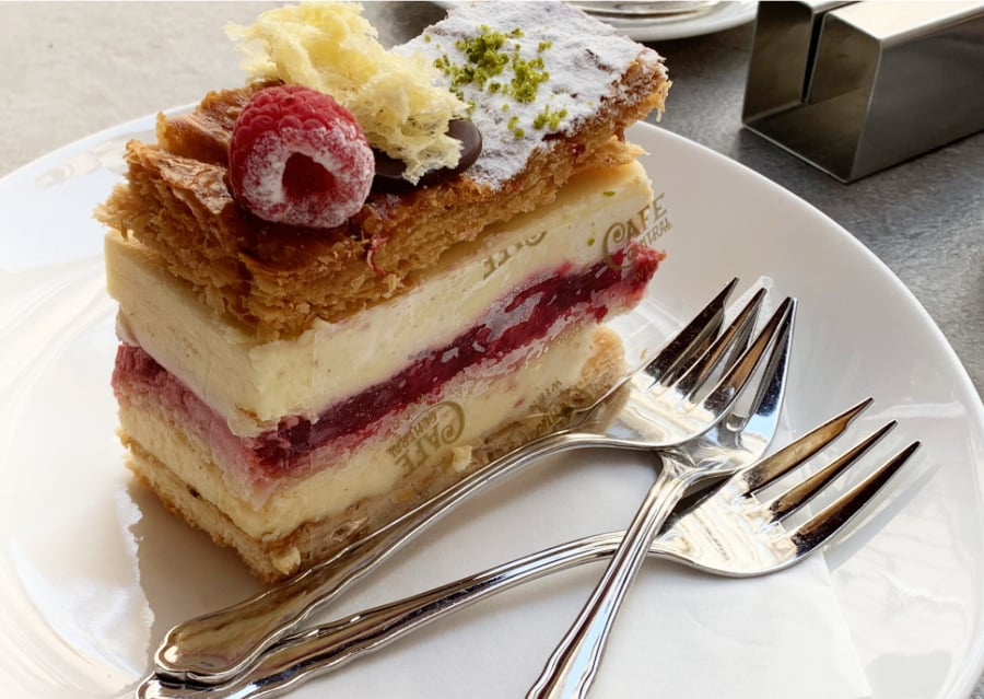 Decadent dessert with layers of cake, custard and raspberry filling sitting on a white plate with three stainless steel forks.