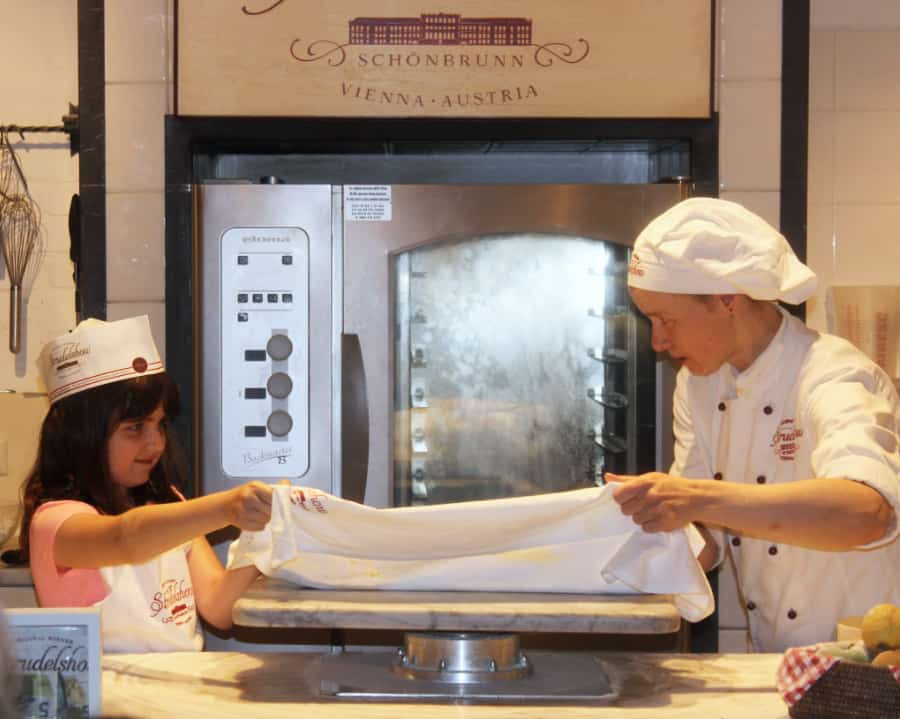 Little girl on the left with an older adult on the right both with white hats and aprons gathering up a white towel to flip the strudel on it over to its side