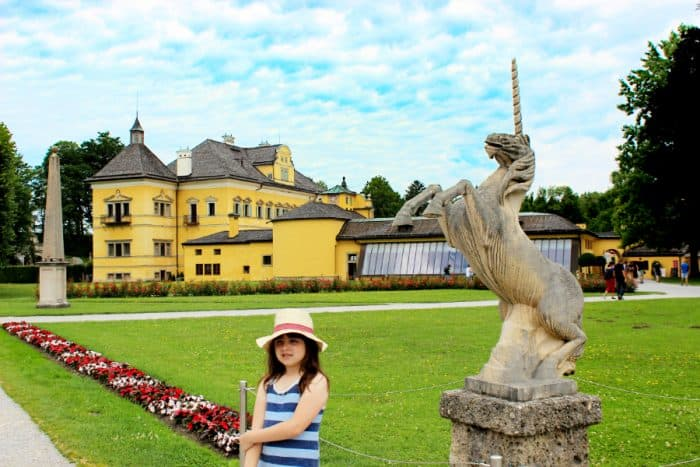 Young girl with sunhat on standing in a garden by a unicorn stone statue in front of a large yellow palace with greenhouse