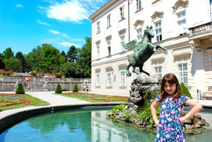 Young girl posing and smiling in front of a fountain with a winged horse in the center surrounded by a white palace and lush gardens with red flowers