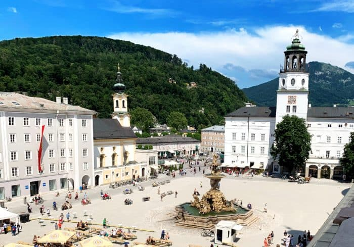 Large European square with center fountain, white baroque buildings at edge of square, people walking around and tree filled mountains in the back with a bright blue sky