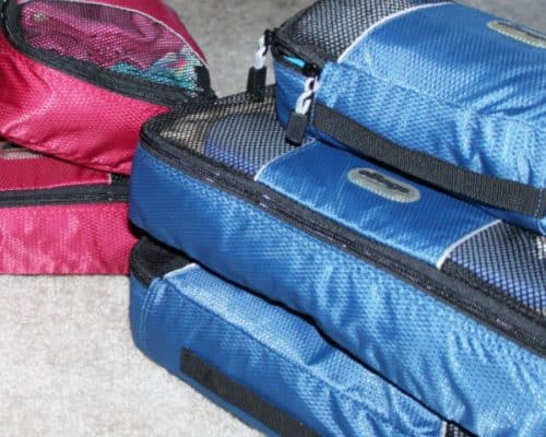 Set of 3 blue packing cubes in foreground with 3 pink packing cubes in background